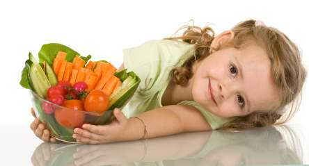 Little girl leaning on the table with a bowl of vegetables - nutrition